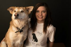 A portrait of a smiling brown haired girl and a tan husky labrador dog. Girl is wearing a white t shirt saying This beauty loves her beast